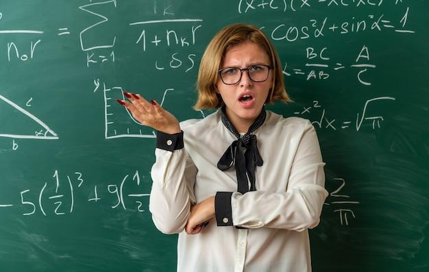 Verwarde jonge vrouwelijke leraar met een bril die vooraan op het schoolbord staat en de hand in de klas verspreidt