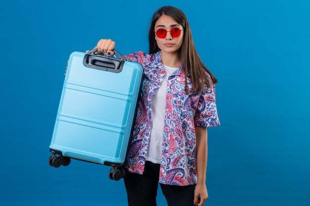 Verwarde jonge vrouwentoerist die rode zonnebril draagt die reiskoffer met boos gelaatsuitdrukking houdt die zich op geïsoleerd blauw bevindt