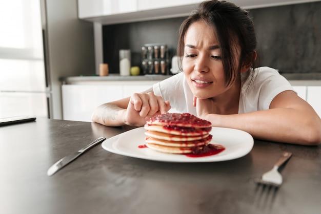 Verwarde jonge vrouwenzitting bij de keuken in huis