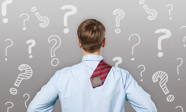 Verwarde, jonge zakenman die veel met krijt getekende vraagtekens bekijkt