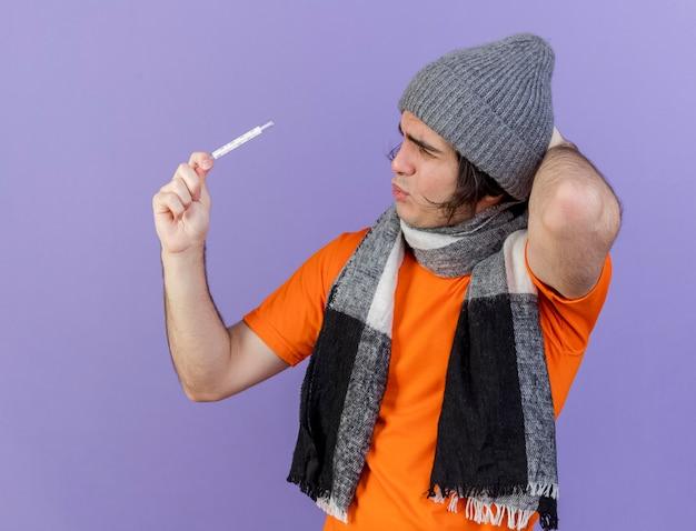 Verwarde jonge zieke man dragen winter hoed met sjaal verhogen en kijken naar thermometer zetten hand achter hoofd geïsoleerd op paars