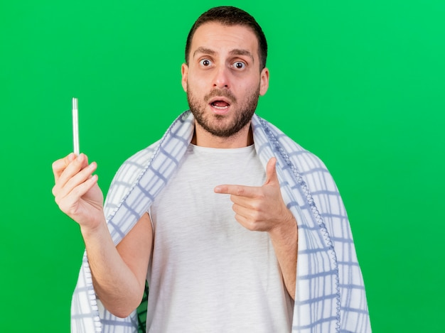 Verwarde jonge zieke man gewikkeld in geruite bedrijf en poinst op thermometer geïsoleerd op groene achtergrond