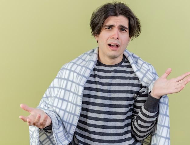 Verwarde jonge zieke man gewikkeld in geruite spreidende handen geïsoleerd op olijfgroen