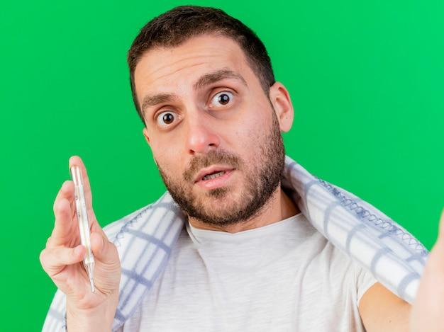 Verwarde jonge zieke man met thermometer verpakt in plaid en camera geïsoleerd op groen te houden