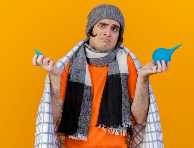 Verwarde jonge zieke man met winter hoed met sjaal gewikkeld in plaid bedrijf klysma's en spreidende handen geïsoleerd op oranje