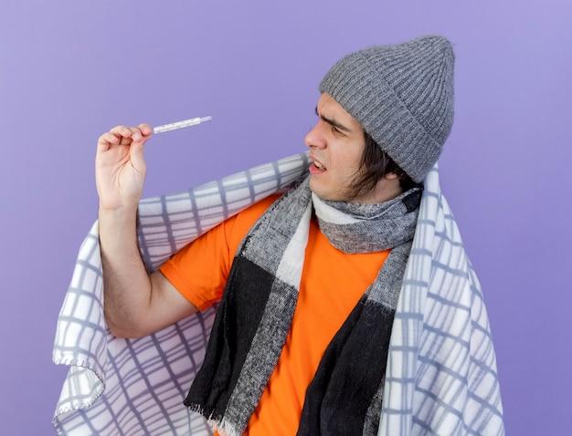 Verwarde jonge zieke man met winter hoed met sjaal verpakt in geruite bedrijf en kijken naar thermometer geïsoleerd op paars