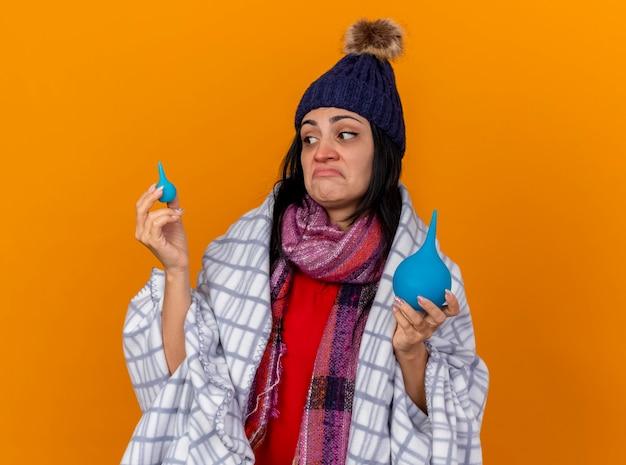 Verwarde jonge zieke vrouw die de wintermuts en sjaal draagt die in geruite klysma's wordt verpakt die kleintje bekijkt dat op oranje muur wordt geïsoleerd Gratis Foto