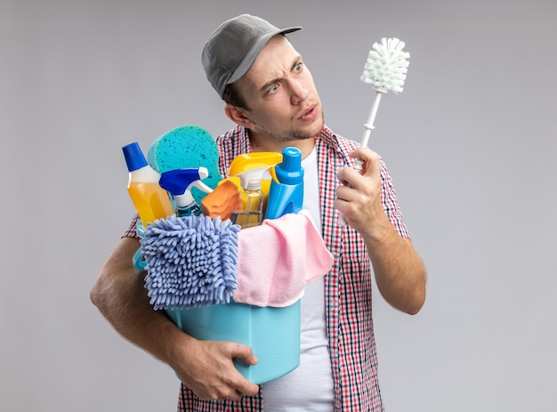 Verwarde jongeman met een dop die een emmer vasthoudt met schoonmaakgereedschap en kijkt naar een borstel in zijn hand geïsoleerd op een witte muur