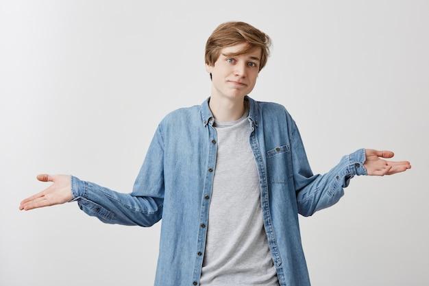 Verwarde jongeman met trendy kapsel en blauwe ogen draagt een demin-shirt over een grijs t-shirt, haalt verbijsterd de schouders op, maakt moeilijke keuze of beslissing in zijn leven, probeert een oplossing te vinden