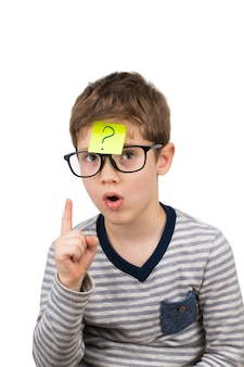Verwarde jongen die met vraagteken op kleverige nota op voorhoofd denken