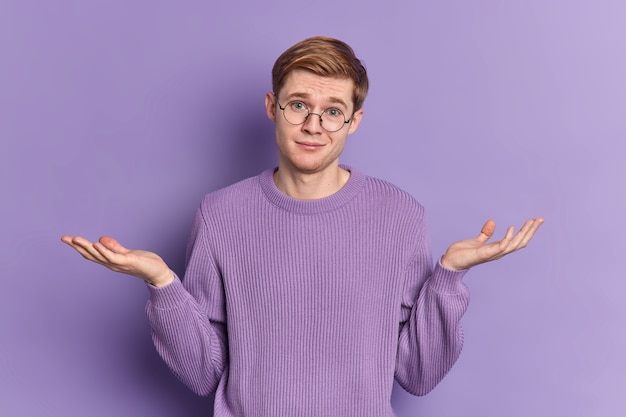 Verwarde jongere haalt zijn schouders op, spreidt zijn handpalmen, staat besluiteloos binnen, gekleed in een casual trui draagt een ronde bril