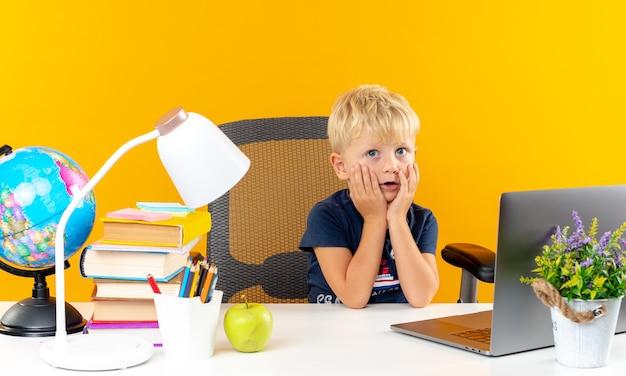 Verwarde kleine schooljongen die aan tafel zit met schoolhulpmiddelen die handen op de wangen leggen