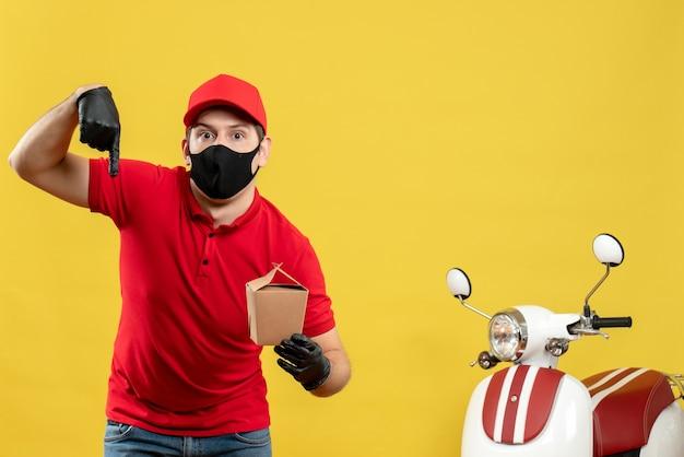 Verwarde koeriersmens in rood uniform die zwarte medische masker en handschoen draagt die orden levert die naar beneden op witte achtergrond wijzen