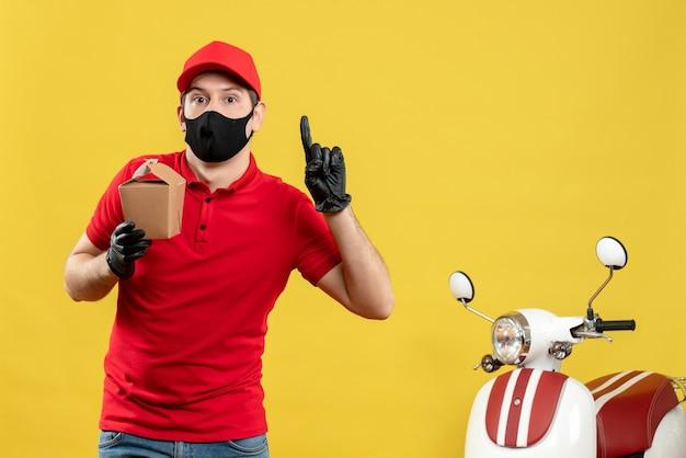 Verwarde koeriersmens in rood uniform die zwarte medische masker en handschoen draagt die orden levert die op witte achtergrond verschijnen