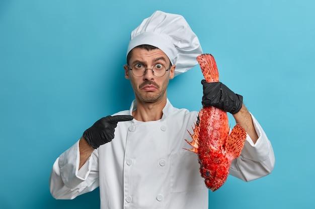 Verwarde kok wijst naar grote rode zeevis, vraagt advies wat te koken van het product, heeft een nieuw recept nodig, draagt een wit uniform
