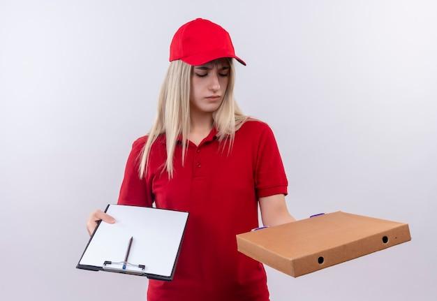 Verwarde levering jonge vrouw, gekleed in rode t-shirt en pet met klembord op zoek naar pizzadoos bij de hand op geïsoleerde witte muur