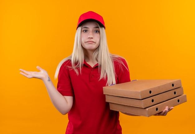Verwarde levering jonge vrouw, gekleed in rode t-shirt en pet met pizzadoos op geïsoleerde oranje muur