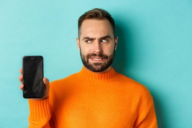 Verwarde man die zijn hoofd kraakt en smartphonescherm laat zien die verbaasd staat over turquoise b...