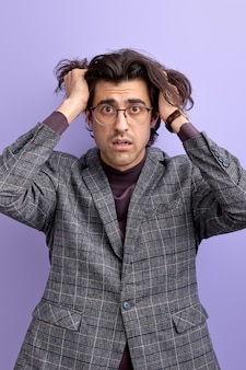 Verwarde man greep hoofd door schok camera kijken met verbaasde gezichtsuitdrukking. geïsoleerde paarse muur
