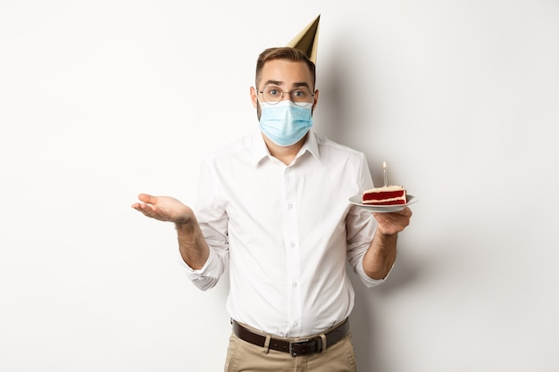 Verwarde man in gezichtsmasker, verjaardagstaart vast te houden en zijn schouders op te halen, staande over witte achtergrond clueless.