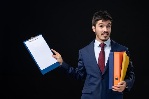 Verwarde man in pak met verschillende documenten en iets vragend op geïsoleerde donkere muur