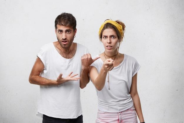 Verwarde man met varkenshaar en stijlvol kapsel wijzend met de vinger naar de vrouw die naast hem staat en probeert haar schuldig te maken. verbaasde mooie vrouw op zoek met ontevredenheid wijzend op jou