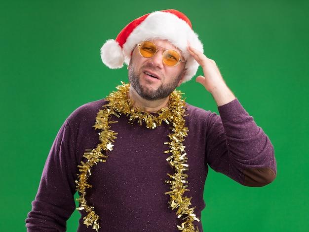 Verwarde man van middelbare leeftijd met kerstmuts en klatergoud slinger rond de nek met een bril kijken naar kant aanraken hoofd geïsoleerd op groene achtergrond