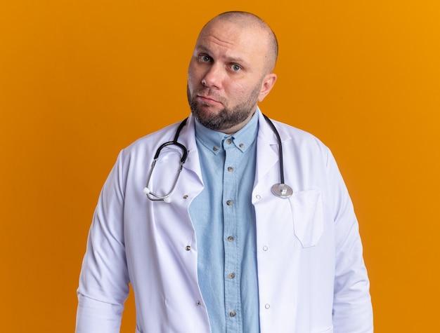 Verwarde mannelijke arts van middelbare leeftijd met een medisch gewaad en een stethoscoop geïsoleerd op een oranje muur