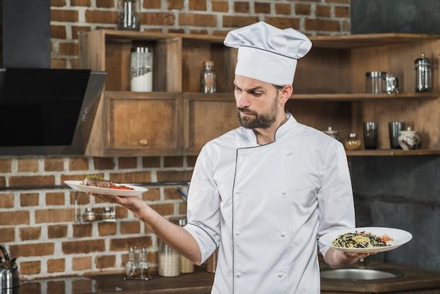 Verwarde mannelijke kok die voorbereide schotels bekijkt