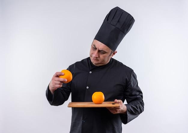 Verwarde mannelijke kok van middelbare leeftijd in eenvormige chef-kok die sinaasappel in scherpe raad houdt en sinaasappel in zijn hand op geïsoleerde witte muur bekijkt