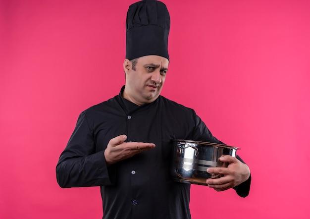 Verwarde mannelijke kok van middelbare leeftijd in eenvormige chef-kok die steelpan in zijn hand op geïsoleerde roze muur met exemplaarruimte toont