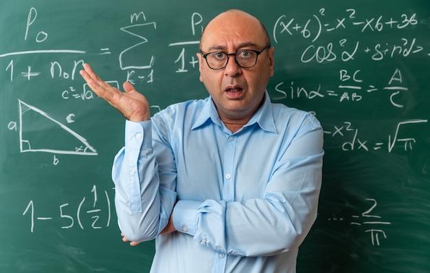 Verwarde mannelijke leraar van middelbare leeftijd met een bril die voor het bord staat en de hand uitspreidt