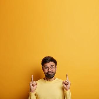 Verwarde millennial ongeschoren man wijst met zijn vingers naar boven, bespreekt promotiedeal, heeft een aarzelende uitdrukking, gekleed in een gele trui, drukt verwondering en keuze uit, kopieer ruimte voor je tekst