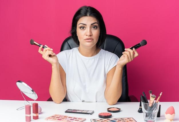 Verwarde mooie vrouw zit aan tafel met make-uptools met poederborstels