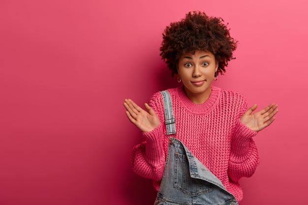 Verwarde, onbewuste vrouw met afro-kapsel, spreidt de handpalmen zijwaarts