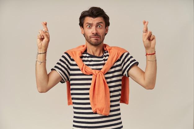 Verwarde, onhandige man met donkerbruin haar en borstelharen. het dragen van een gestreept t-shirt en een trui die op de schouders is vastgebonden. houdt de vingers gekruist, doe een wens