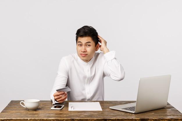 Verwarde, onzekere jonge aziatische kerel, kantoormedewerker, zittafel bij laptop, documenten, aarzelend krabben, perplex houden met creditcard, geen contant geld voorstellen geld sturen via bank