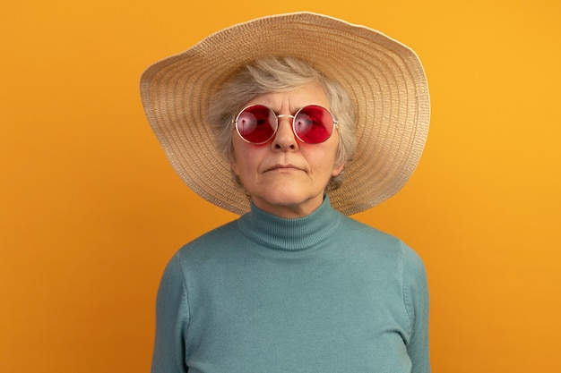 Verwarde oude vrouw met blauwe coltrui, strandhoed en zonnebril geïsoleerd op oranje muur