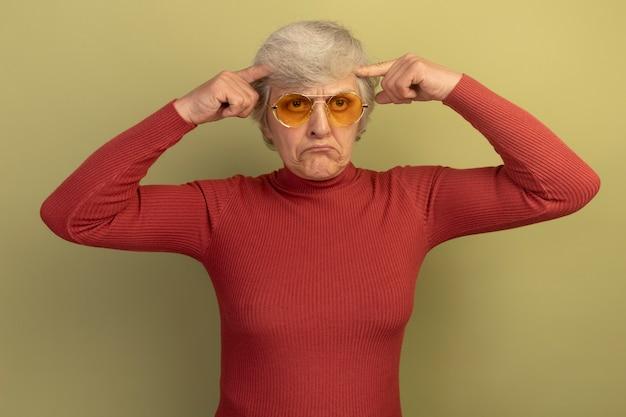 Verwarde oude vrouw met een rode coltrui en een zonnebril die er recht uitziet en een denkgebaar doet dat op een olijfgroene muur is geïsoleerd