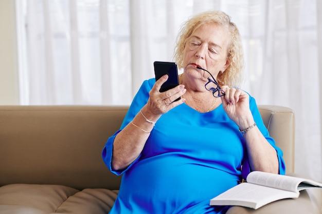 Verwarde oude vrouw met smartphone