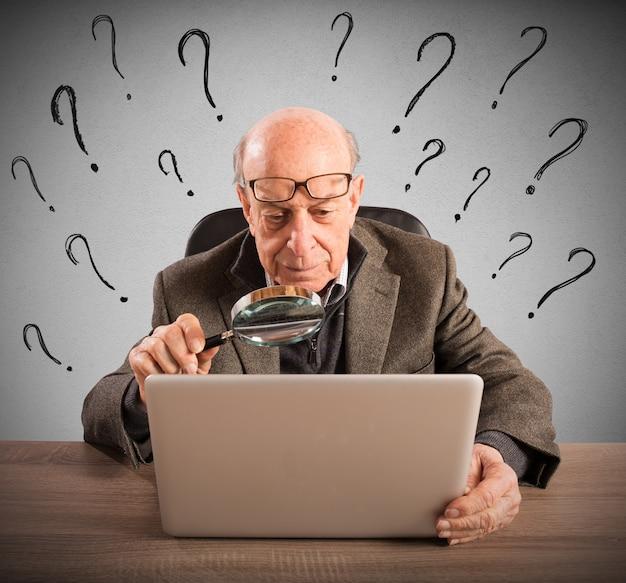 Verwarde oudere man kijkt naar de computer