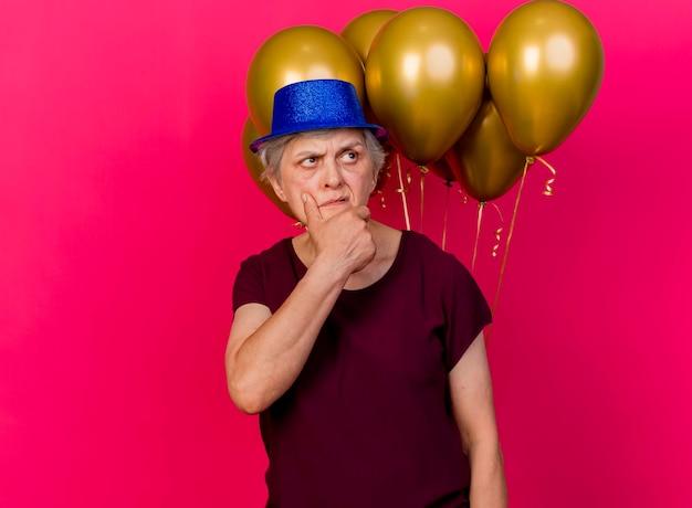 Verwarde oudere vrouw die feestmuts draagt voor heliumballons die kin houden die kant op roze houden