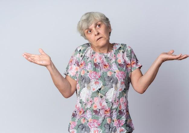 Verwarde oudere vrouw houdt handen open kijkend naar kant geïsoleerd op een witte muur