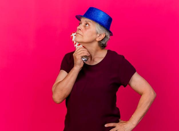Verwarde oudere vrouw met feestmuts houdt confetti kanon opzoeken op roze