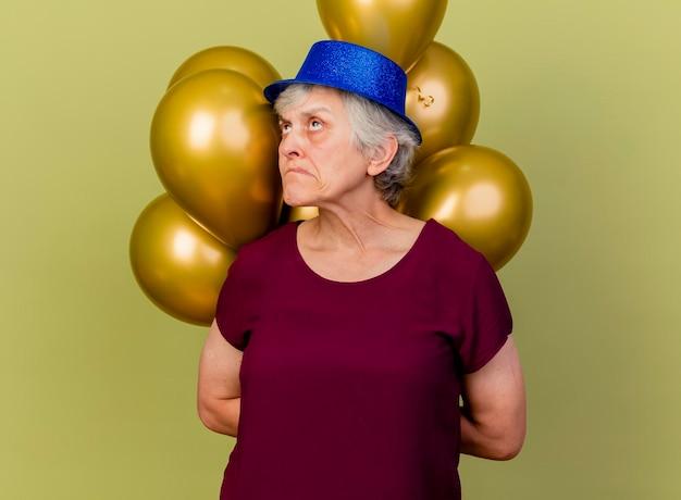 Verwarde oudere vrouw met feestmuts houdt helium ballonnen achter opzoeken op olijfgroen