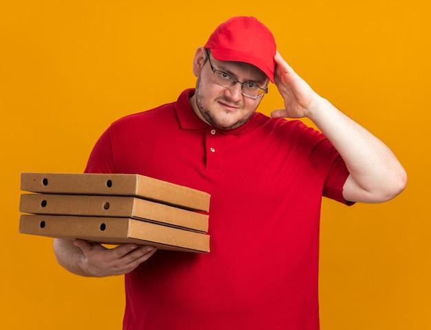 Verwarde overgewicht jonge bezorger in optische glazen pizzadozen te houden en hand op het hoofd te zetten geïsoleerd op oranje muur met kopie ruimte