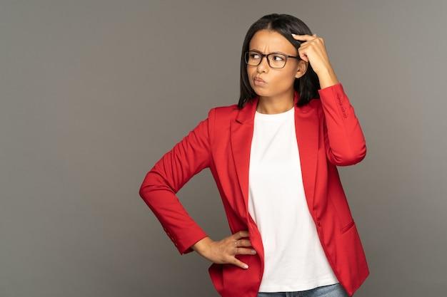 Verwarde, peinzende afro-amerikaanse zakenvrouw die met haar hoofd wrijft en naar de kopieerruimte kijkt voor oplossing