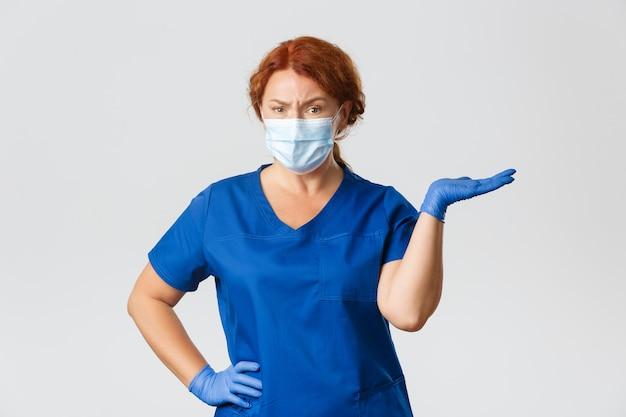 Verwarde sceptische vrouwelijke arts, tandarts in scrubs, gezichtsmasker en handschoenen, schouderophalend, naar rechts wijzend en fronsen teleurgesteld