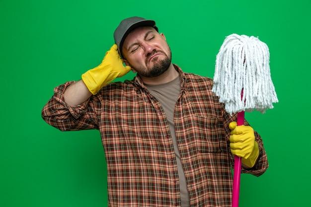 Verwarde schonere man met rubberen handschoenen die mob vasthoudt en bekijkt