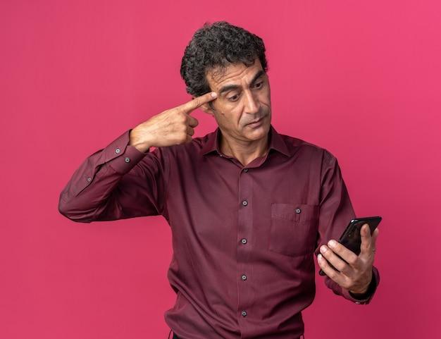 Verwarde senior man in paars shirt met smartphone die ernaar kijkt en met wijsvinger naar zijn slaap wijst die over roze staat